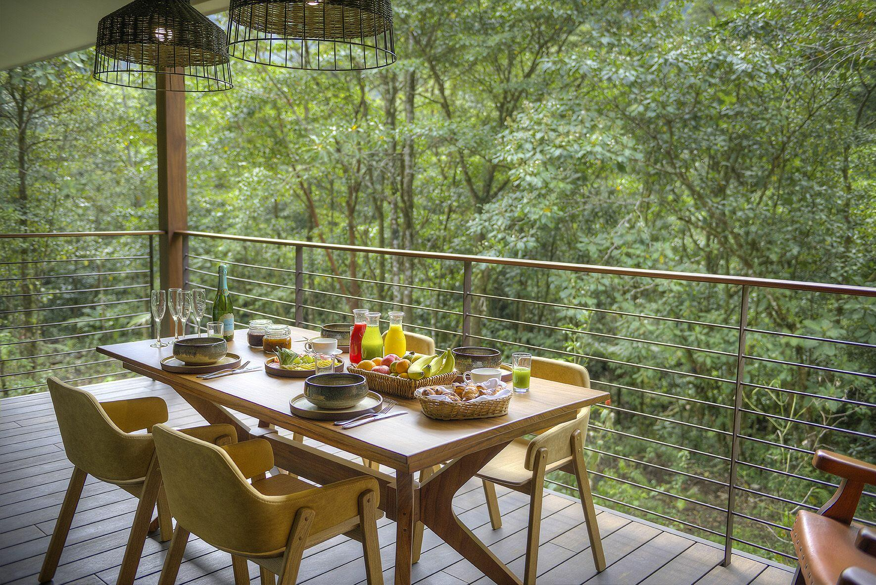 balcony with dining table and forest view