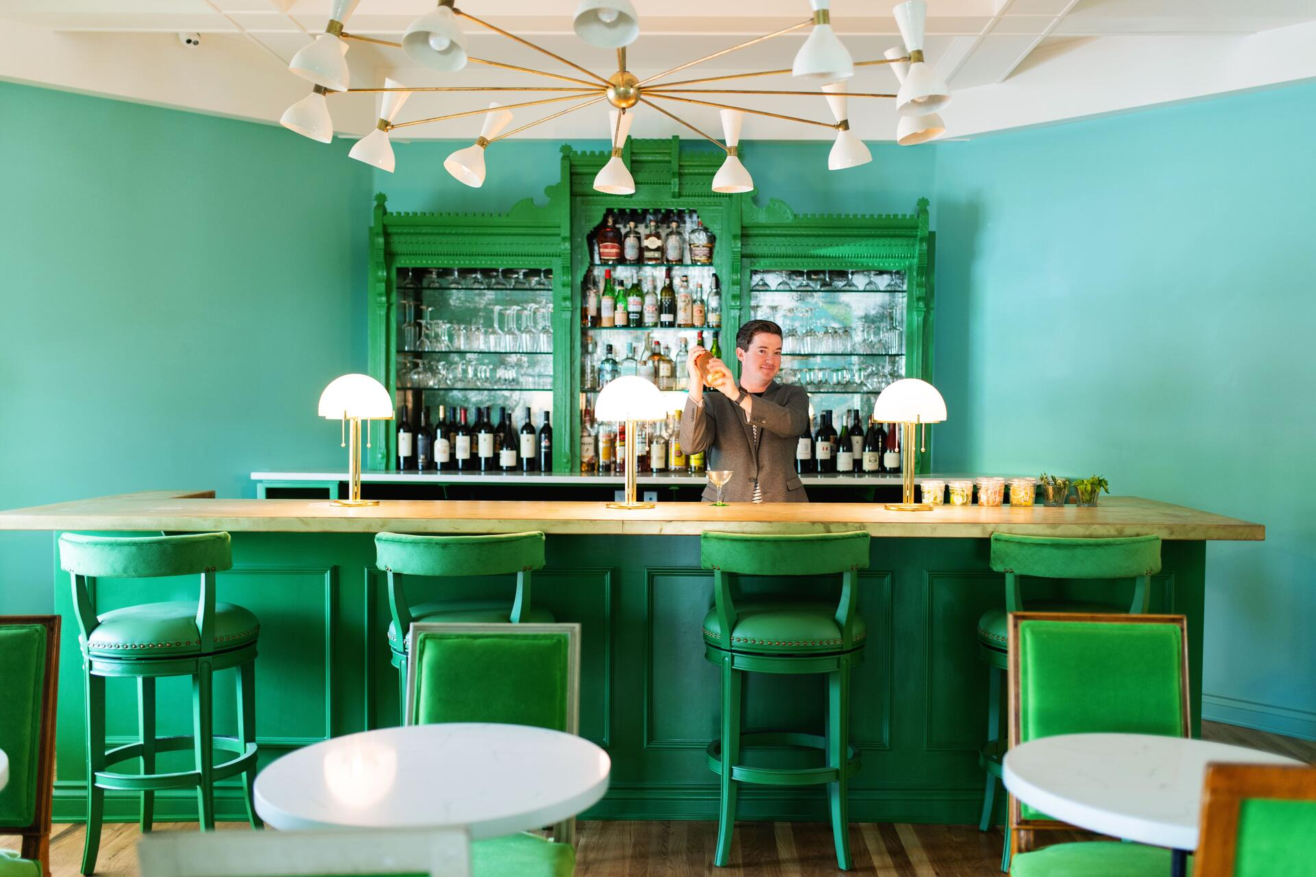 bartender at a green bar in a blue room