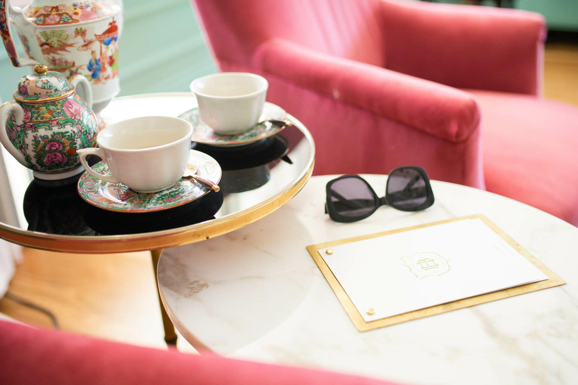 table with sunglasses next to pink chair