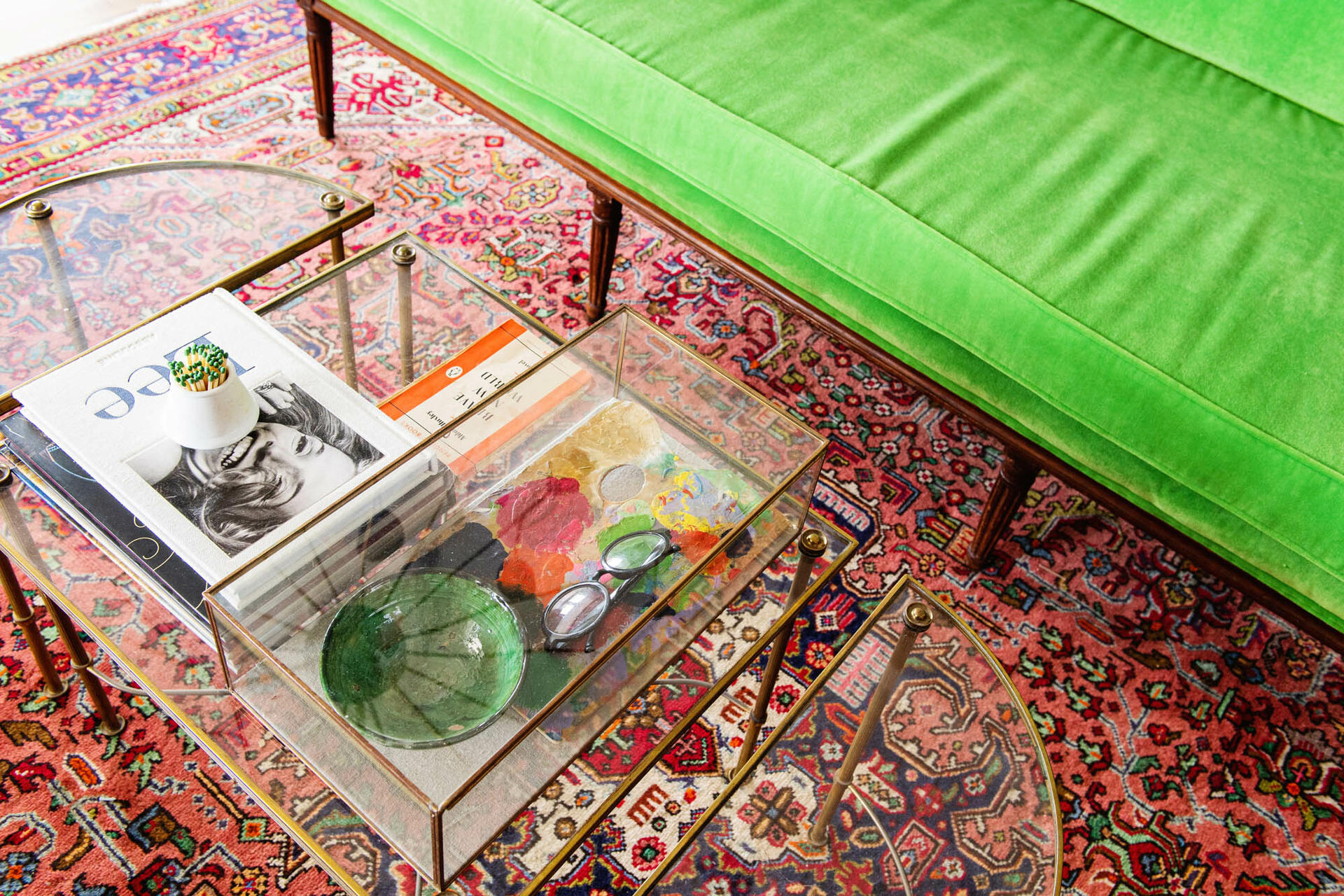red carpet, glass table and green sofa couch