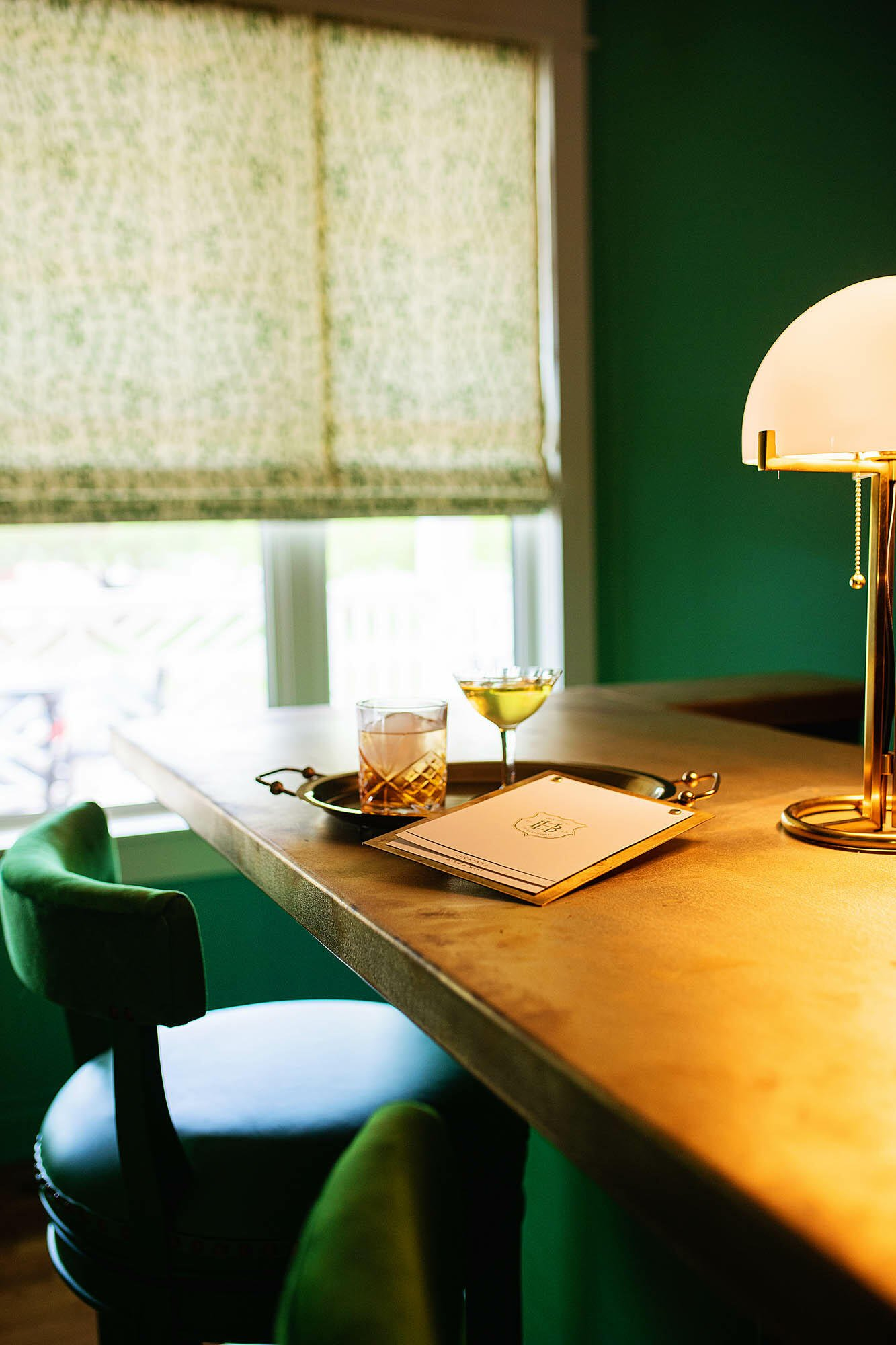 green chair at table with whiskey glass