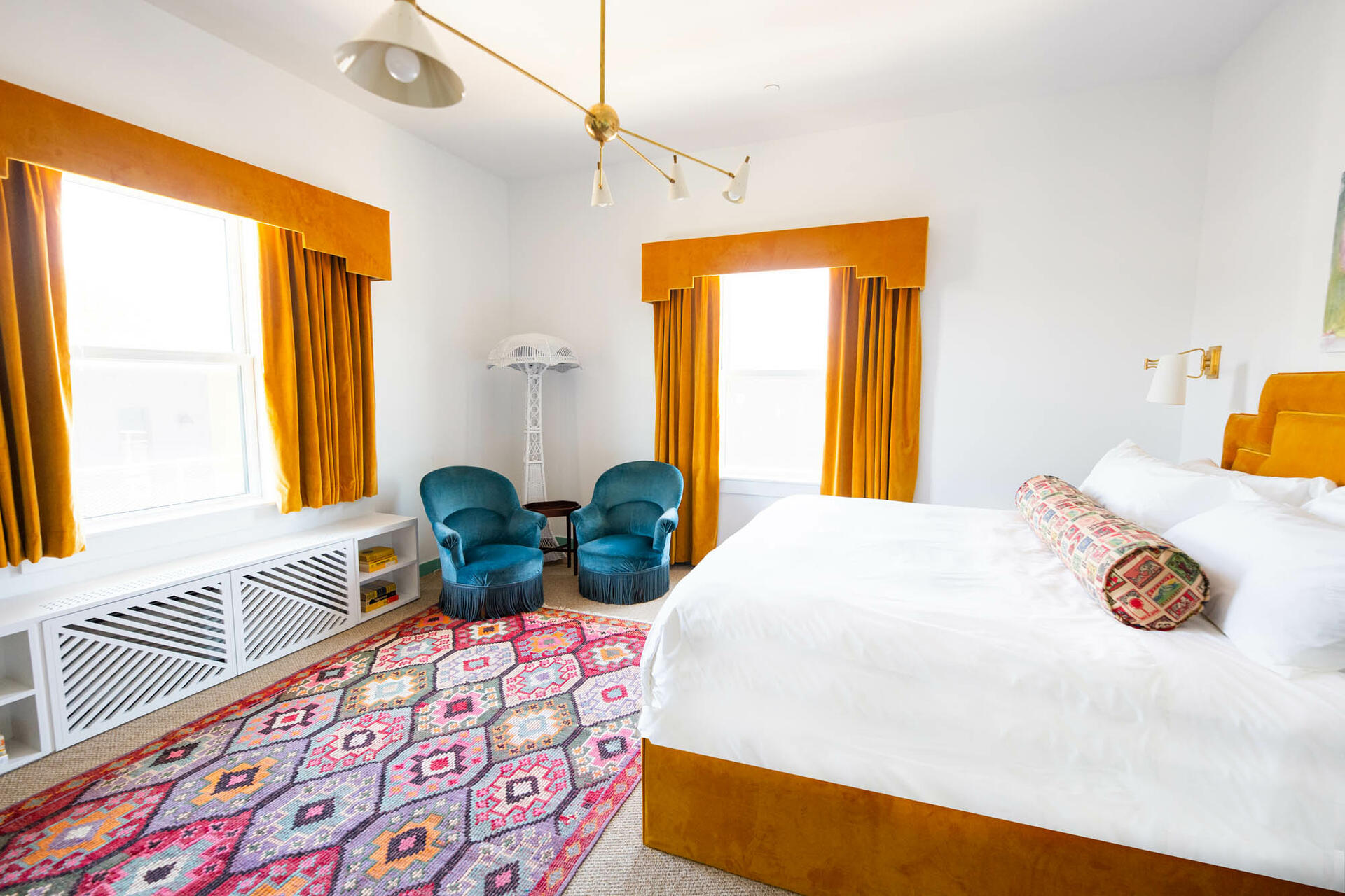 bed with orange bedframe in room with orange window curtains