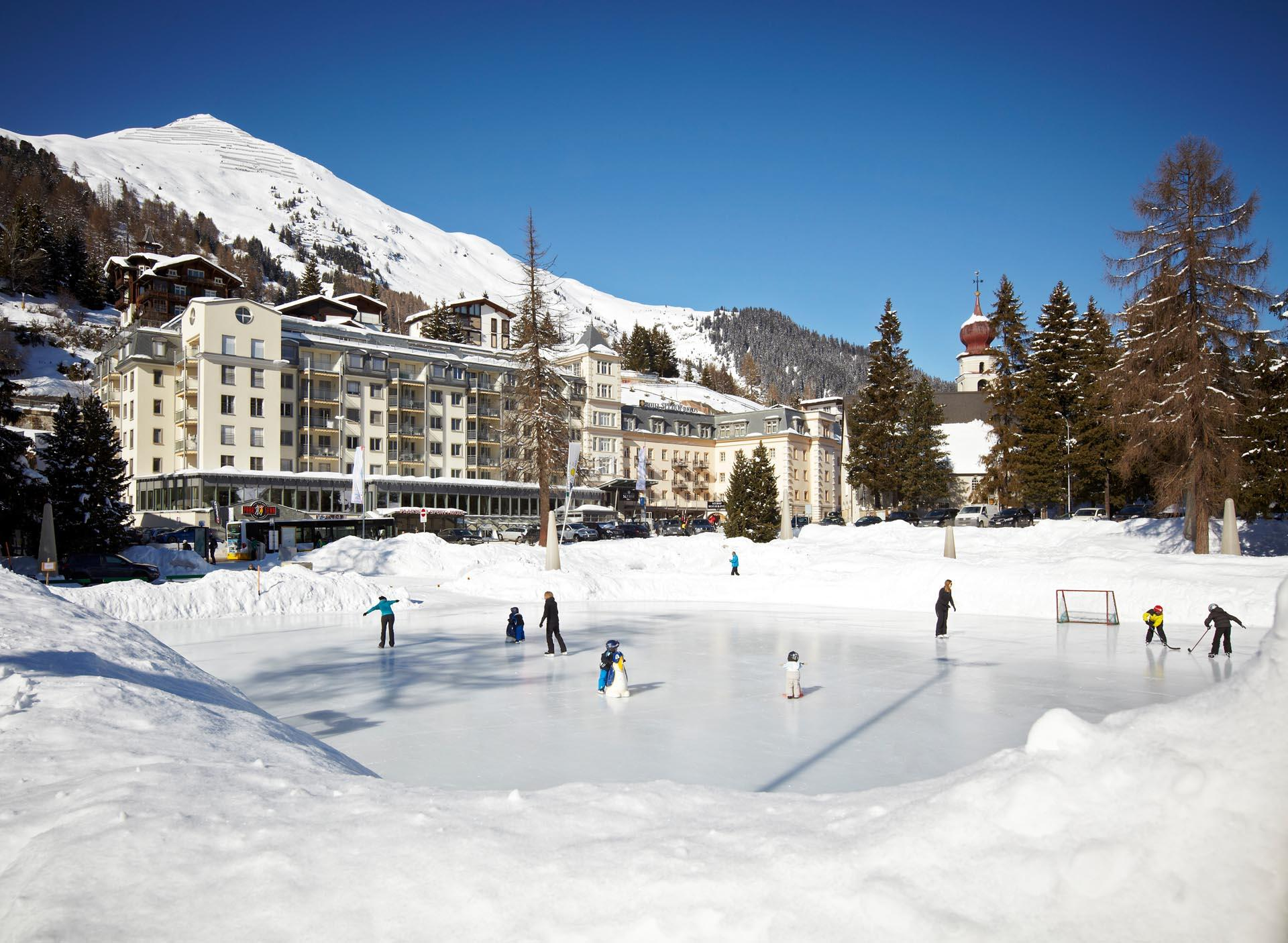 people skating on the frozen lake in front of the Precise Seehof