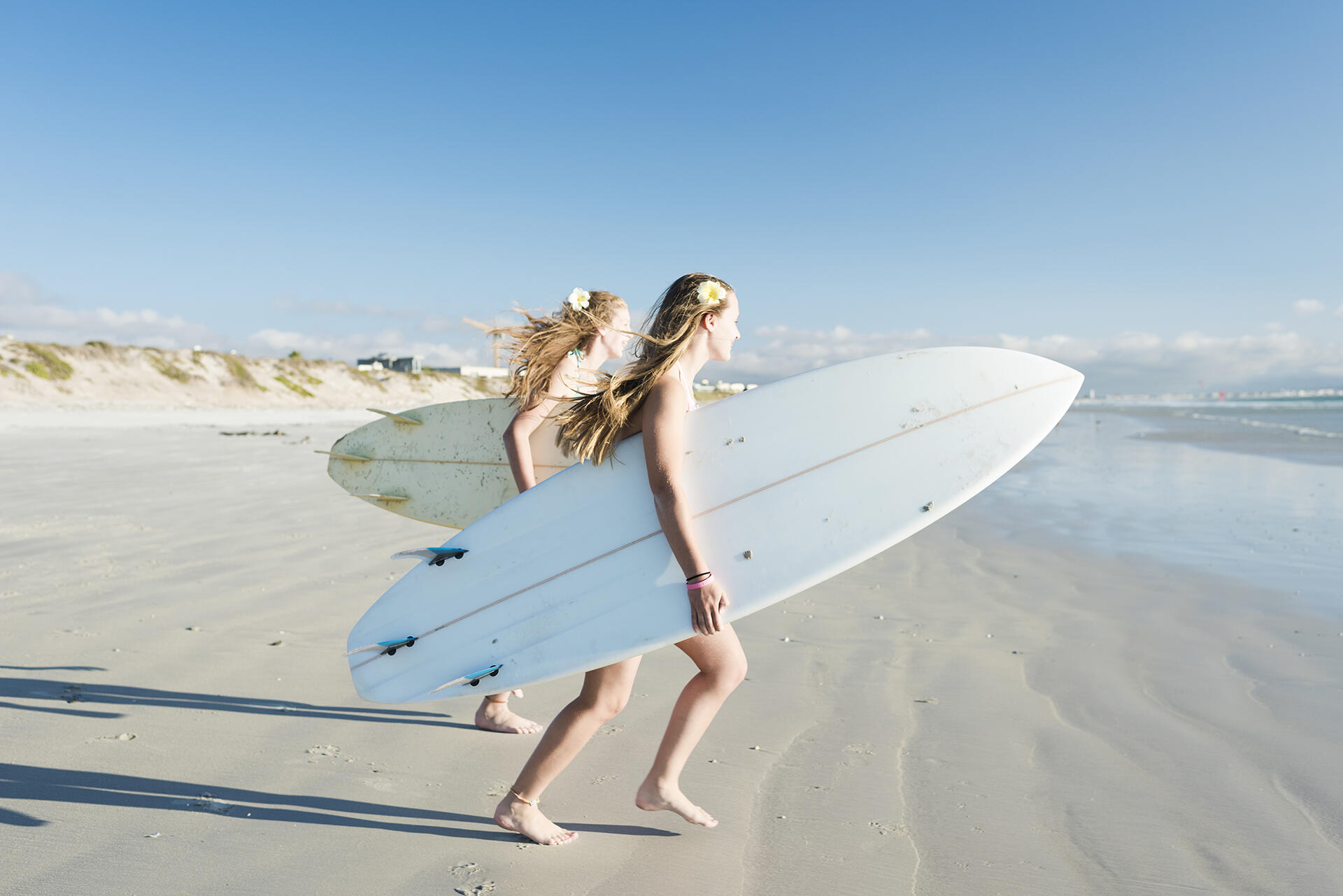 Two girls holding surfboards and walking toward the water in Day