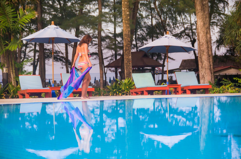 Lady walking by the swimming pool at Amora Hotel