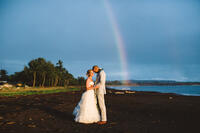 wedding photo on the beach located at Waimea Plantation Cottages with a rainbow in the background