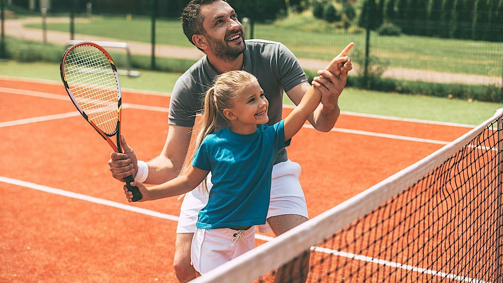 Father and daughter playing tennis at the tennis court in Mundo Imperial