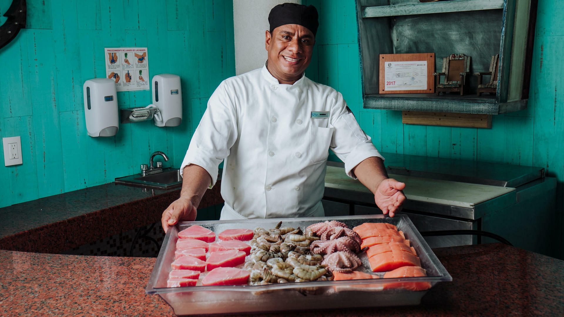 Chef holding meat at Acua Restaurant in Mundo Imperial