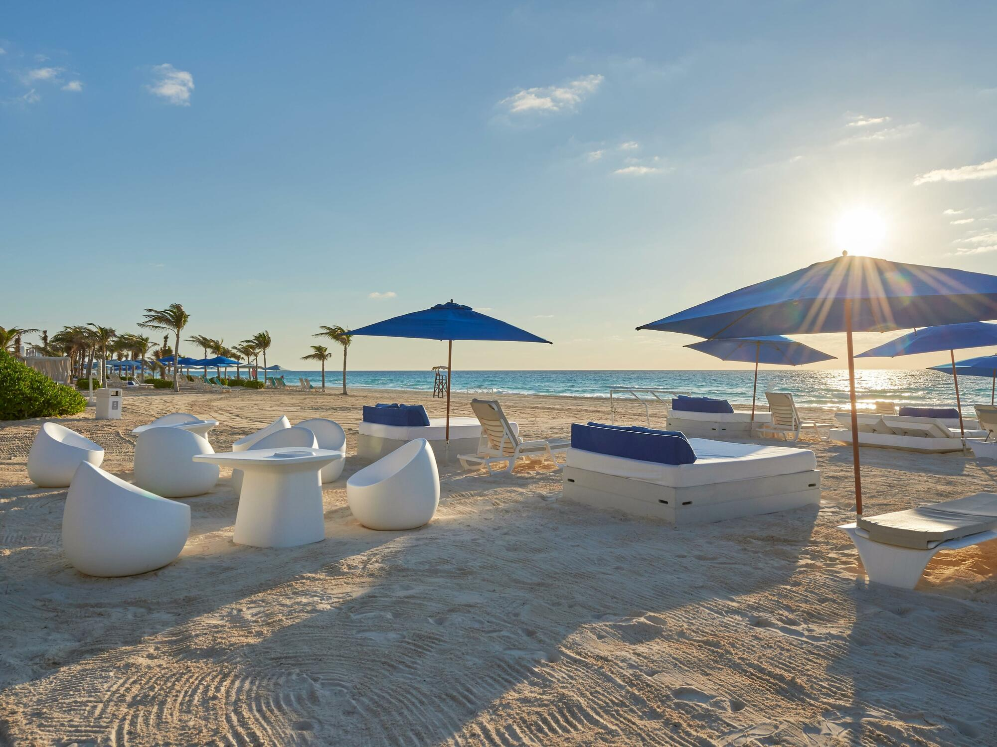 A beach with lounge chairs in the Cancún city