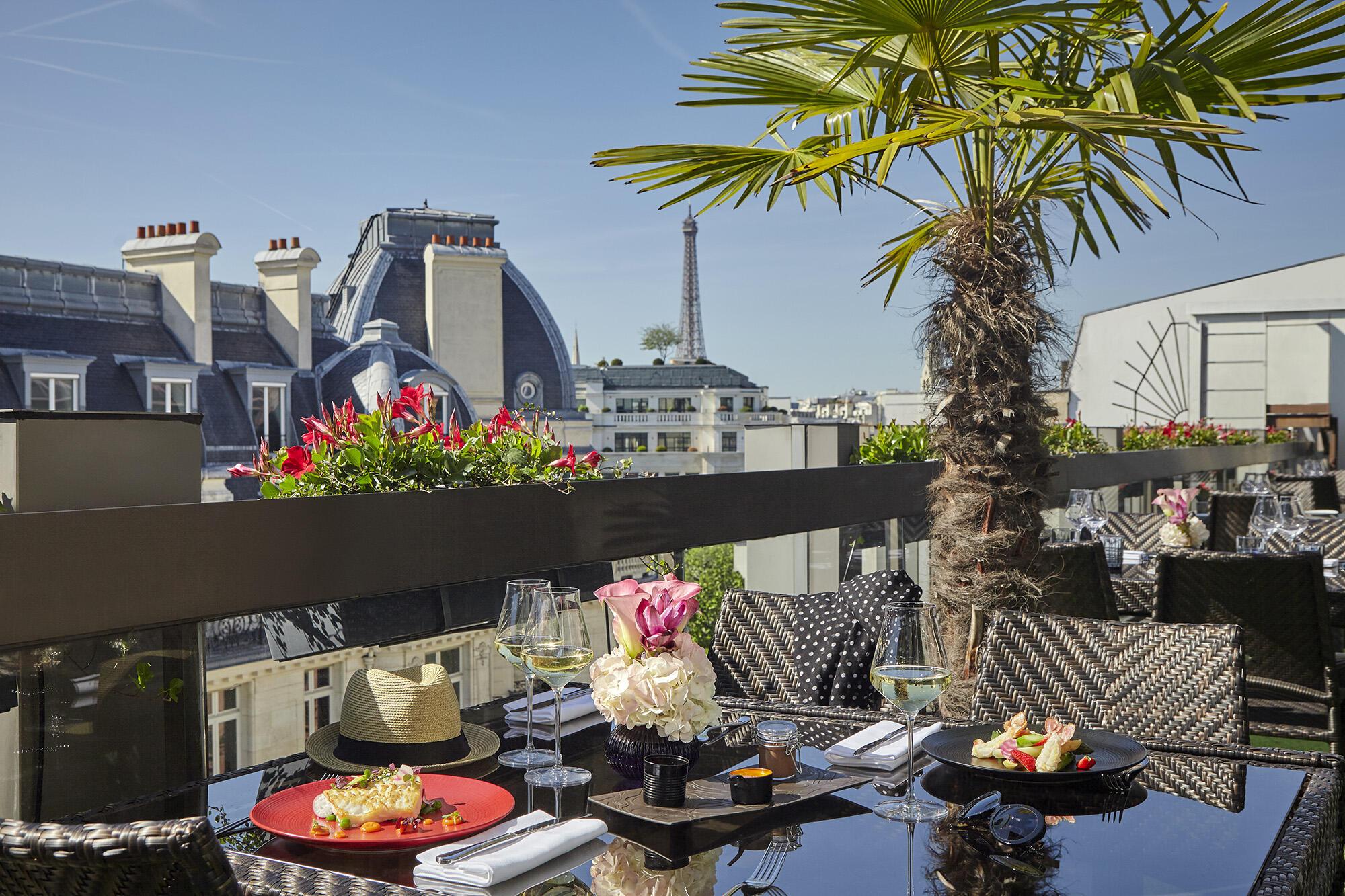 Terrasse offrant une vue sur la tour Eiffel avec plats et boisso