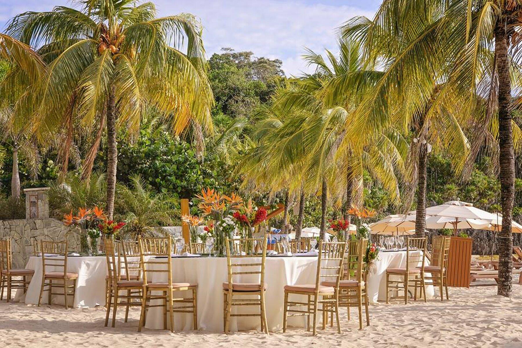 tables set on beach near palm trees