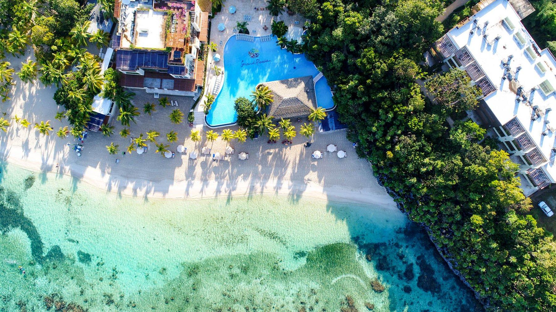 aerial view of large building and pool on the beach