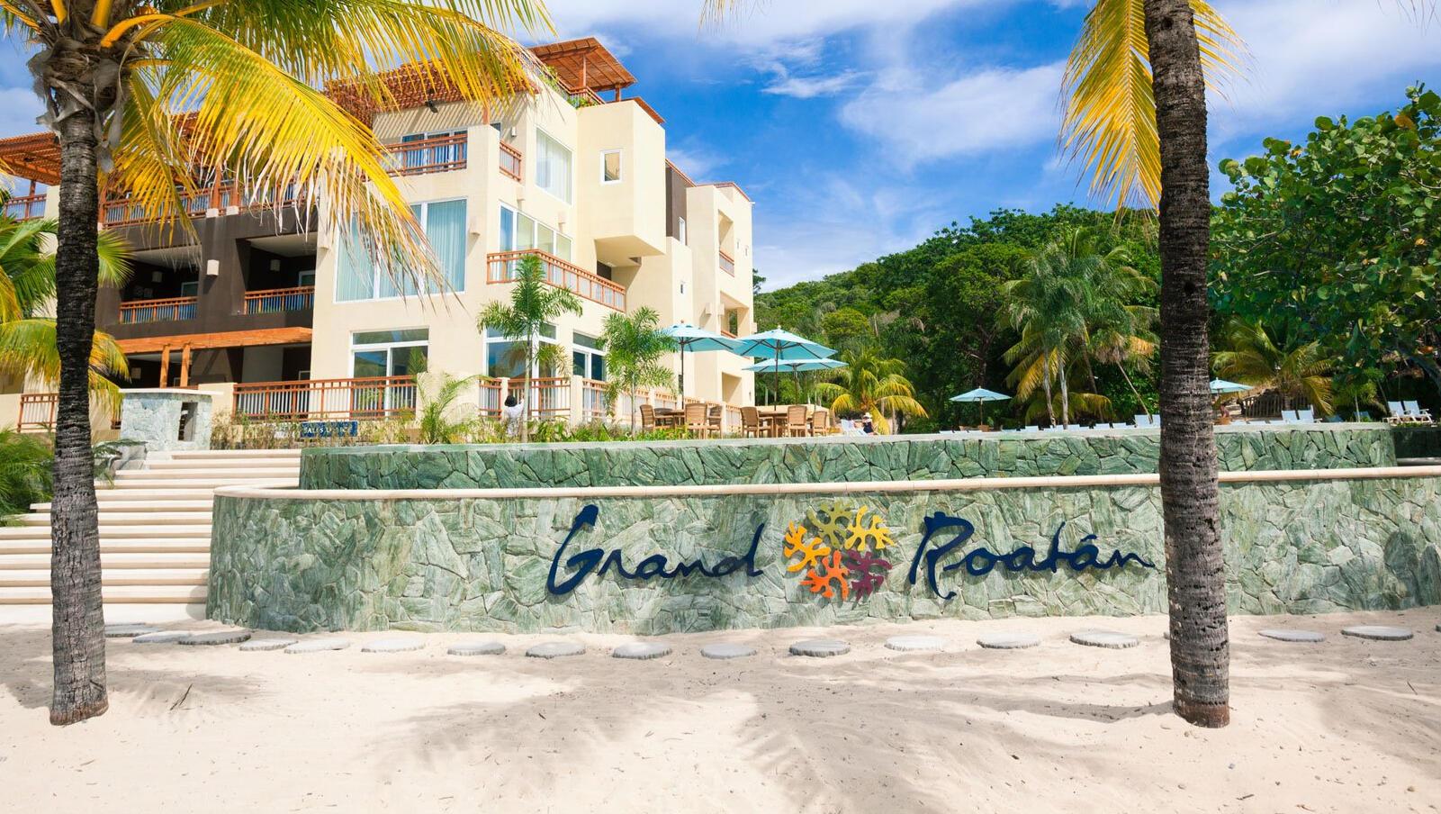 hotel on the beach with grand roatan logo