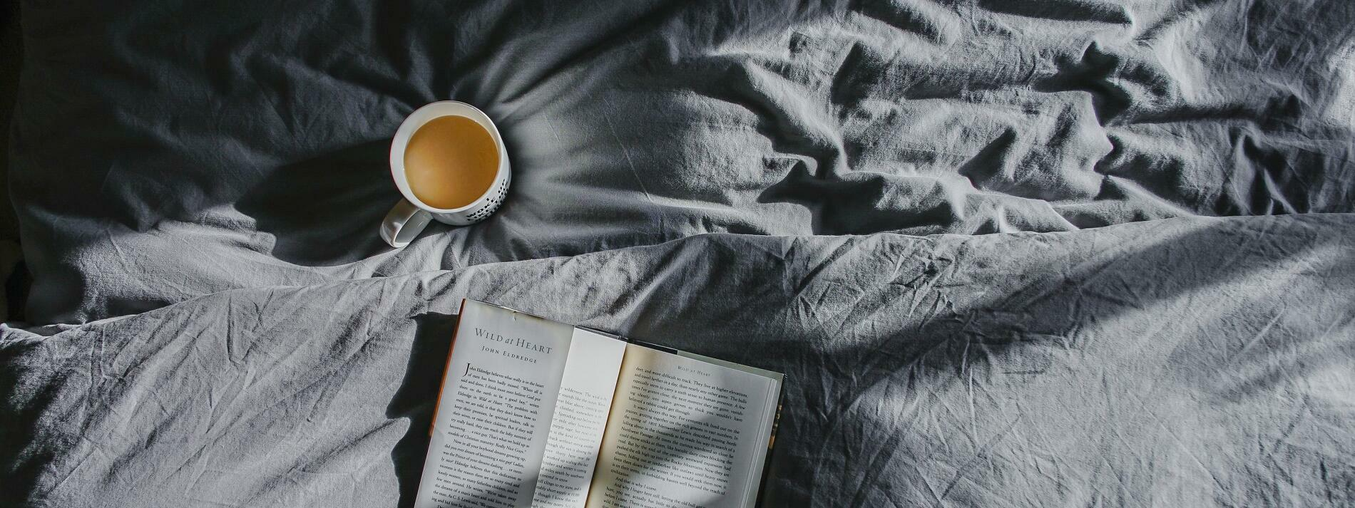 A bed with a cup of tea and a book