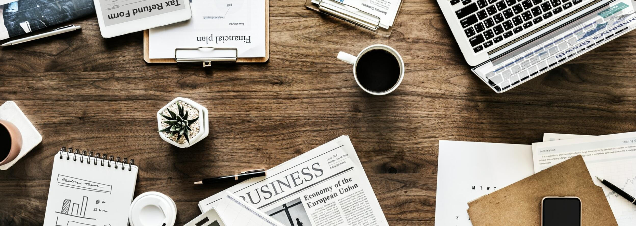 A table with newspapers, a laptop, reports and a coffee mug