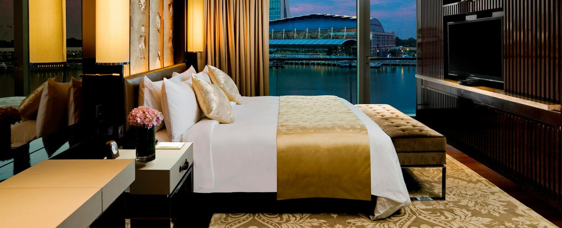 A room with one king bed and a night city view