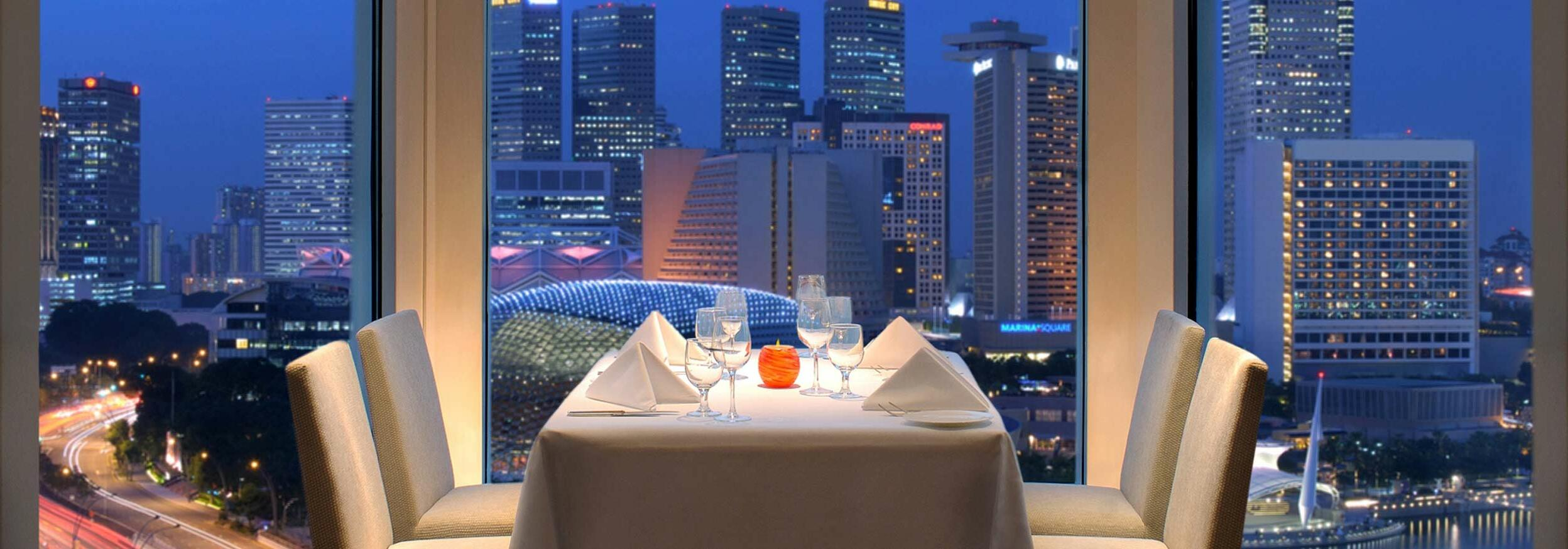 An indoor arranged dining area with a night city view