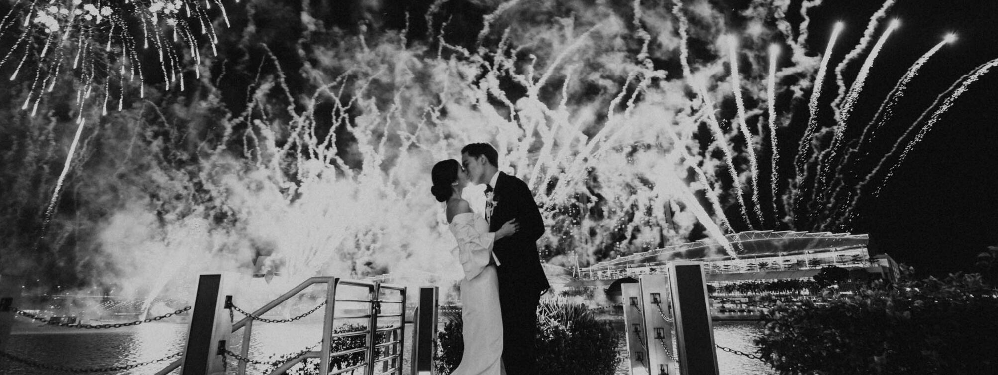 Bride and groom is kissing under fireworks