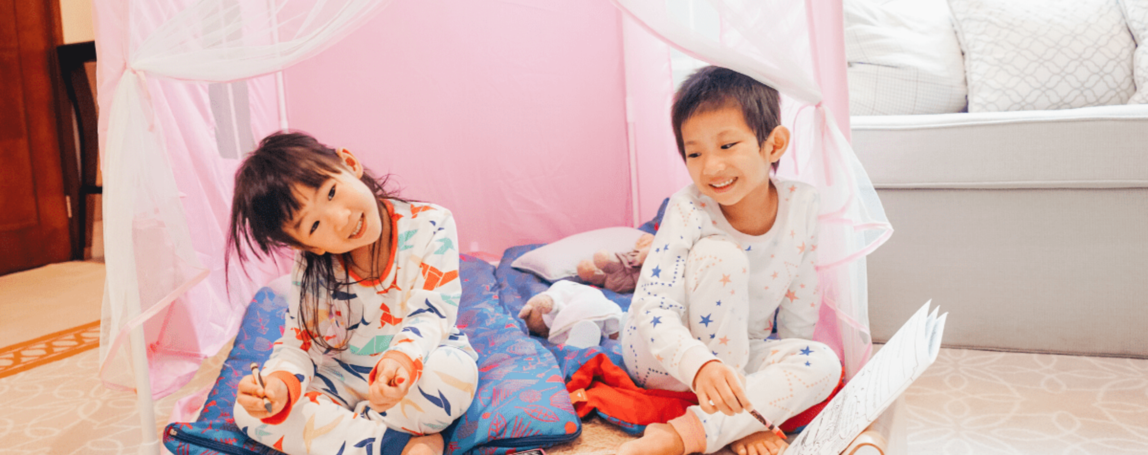 Two kids in pyjamas under a small tent in a room