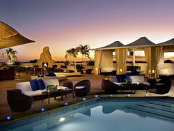 rooftop pool with lounge chairs and tables at dusk
