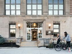 woman biking in front of hotel grinnell