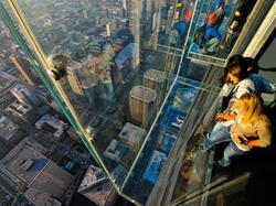 Women stepping onto clear deck overlooking city at Skydeck