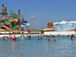 people swimming in large pool with water slide in background