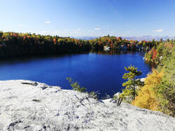 Bright blue lake surrounded by fall trees