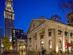 quincy market at night with skyline in background