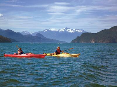 Two kayakers on lake with mountains in the background.