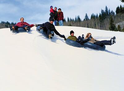 Group tubing down snowy hill