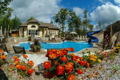 Pool area with slide and colorful floral landscaping