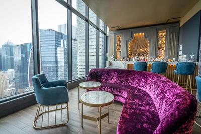 lounge area with purple seat and city skyline through window