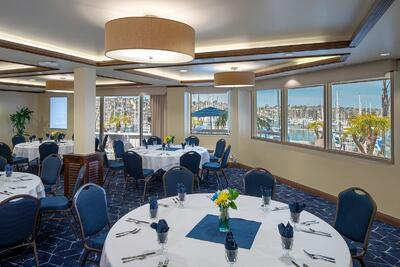 Tables and chairs in dining area with marina view