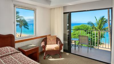 bed and chair in hotel room with balcony overlooking beach and p