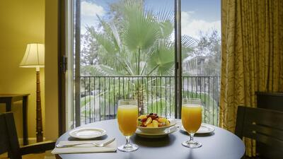 two glasses of orange juice on round table with window and trees