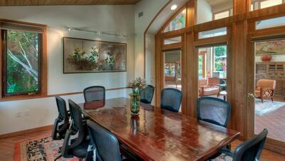wooden conference table with black chairs
