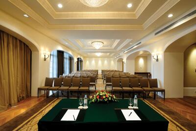 A multi-purpose hall lined with chairs and a reception table at