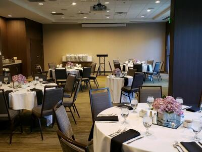 large conference room with circular tables with flower centerpie
