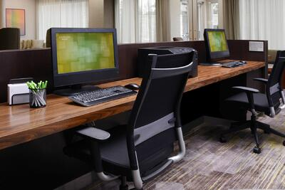 business center with large desk, two computers and two chairs