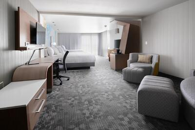room with large bed, accent chairs and work desk