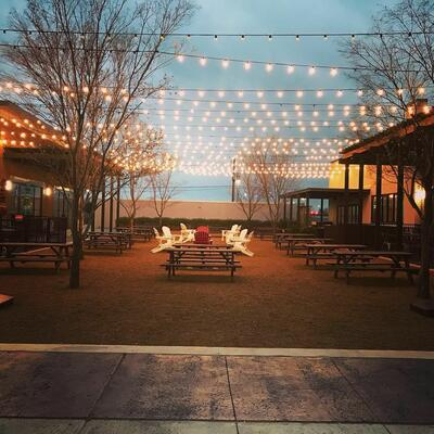 outdoor area with picnic tables and hanging lights