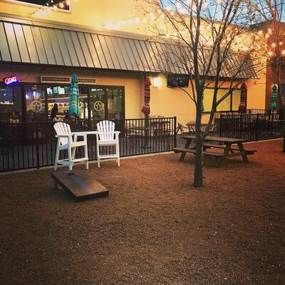outdoor area with adirondack chairs and cornhole station