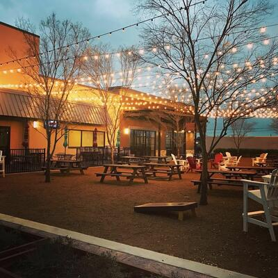 outdoor area with picnic tables and string lights
