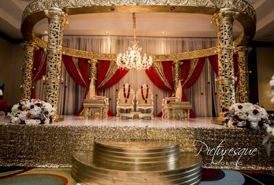 indian wedding gold altar with red curtain draping