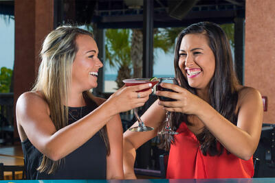 two women cheers cocktails