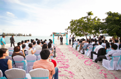 Beachfront wedding with a married couple and guests