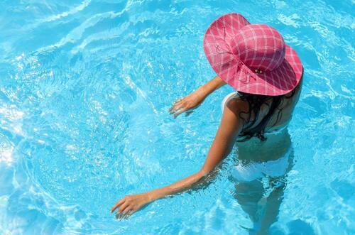 Girl in pool with beach hat