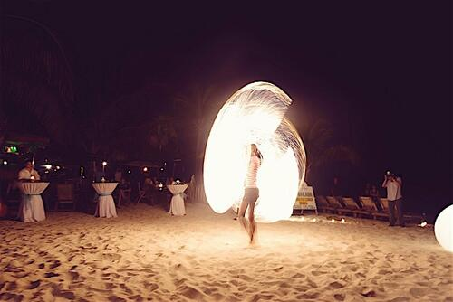 person performing fire show at beach