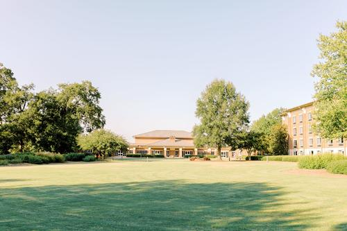 green field with college buildings in background